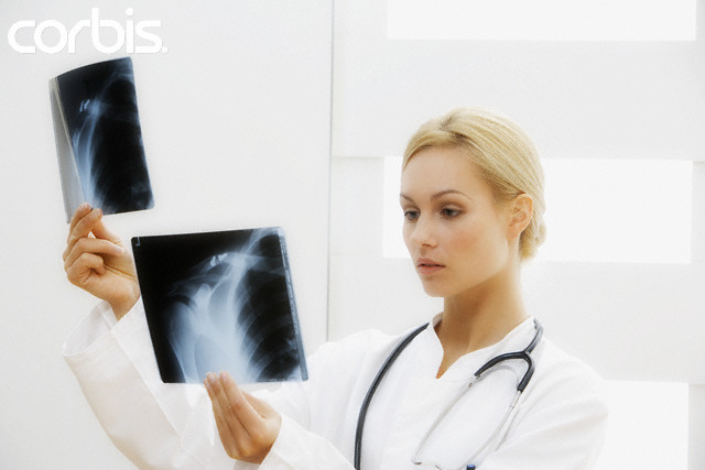 Doctor Looking at X-Rays --- Image by © Thomas Roepke/Corbis
