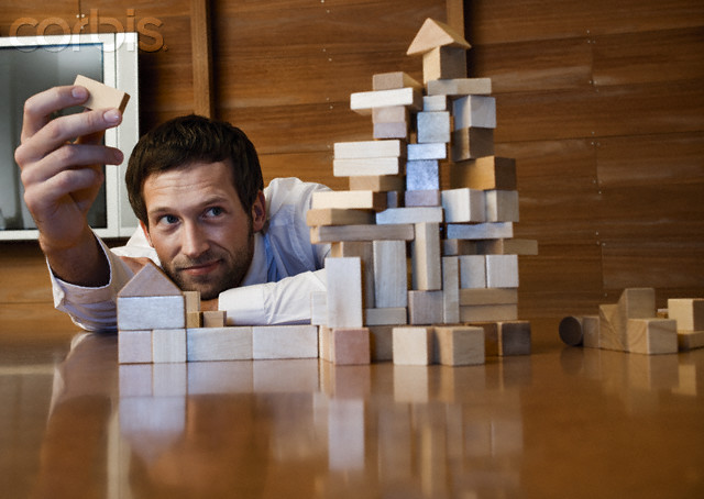 Young businessman constructing a building of blocks of wood --- Image by © Holger Scheibe/Corbis