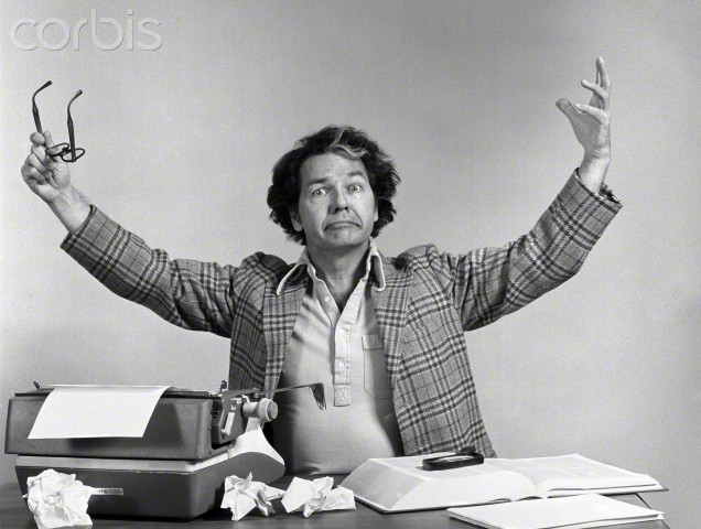 23 Sep 1976 --- 1970s MALE WRITER AT DESK TYPEWRITER CRUMPLED PAPERS ARMS UP IN AIR EXASPERATED EXPRESSION INDOOR LOOKING AT CAMERA --- Image by © H. ARMSTRONG ROBERTS/Corbis