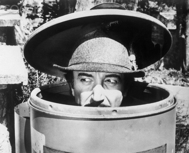 01 Jan 1976, London, England, UK --- Inspector Jacques Clouseau (Peter Sellers) hides in a trash can in The Pink Panther Strikes Again. --- Image by © Bettmann/CORBIS