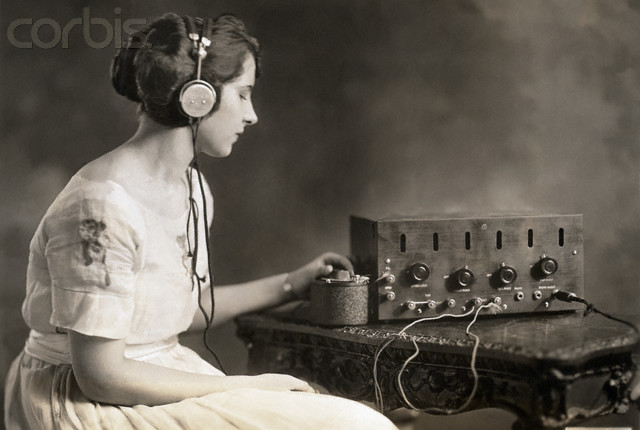 Washington, DC, USA --- Evelyn C. Lewis, Miss Washington 1921, listens to the radio. She tunes in by adjusting the condenser. --- Image by © Corbis