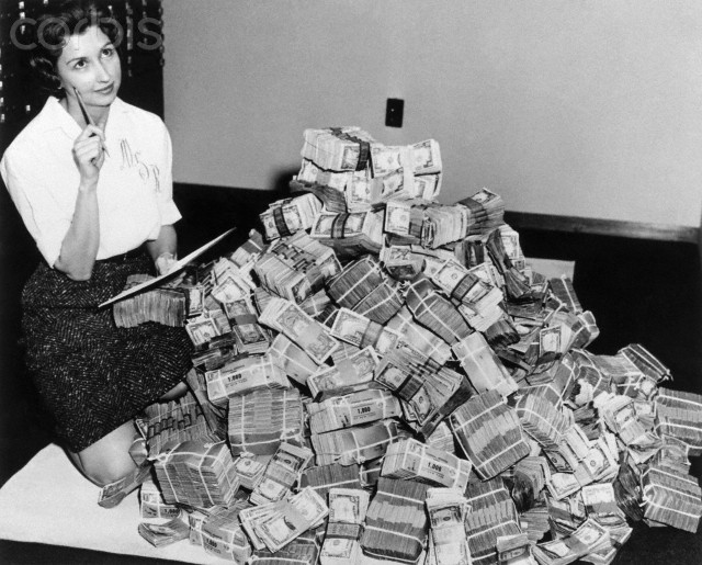20 Feb 1961, Elizabeth, New Jersey, USA --- Marie Reed of the Federal Savings and Loan Association sits next to a million dollars in cash. --- Image by © Bettmann/CORBIS